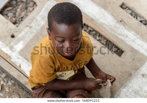 ACCRA, GHANA - JAN 8, 2017: Unidentified Ghanaian little boy in mustard shirt holds a couple of rocks in his hands. Children of Ghana suffer of poverty due to the economic situation