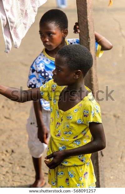 ACCRA, GHANA - JAN 8, 2017: Unidentified Ghanaian girl in yellow suit looks away on the street. Children of Ghana suffer of poverty due to the economic situation
