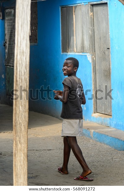 ACCRA, GHANA - JAN 8, 2017: Unidentified Ghanaian girl walks in the street. Children of Ghana suffer of poverty due to the difficult economic situation