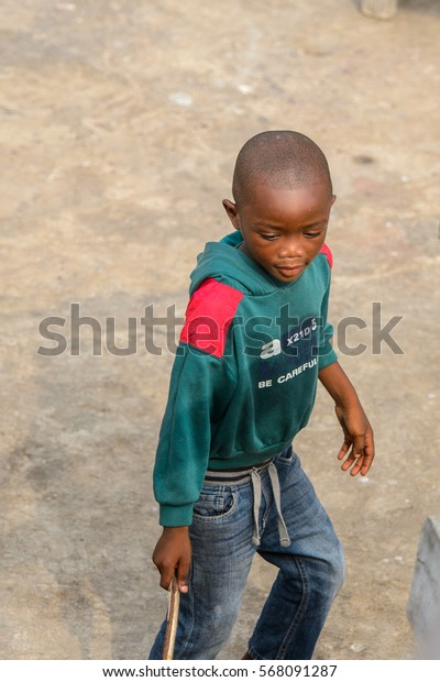 ACCRA, GHANA - JAN 8, 2017: Unidentified Ghanaian boy in celabon sweater holds a wooden stick. Children of Ghana suffer of poverty due to the economic situation