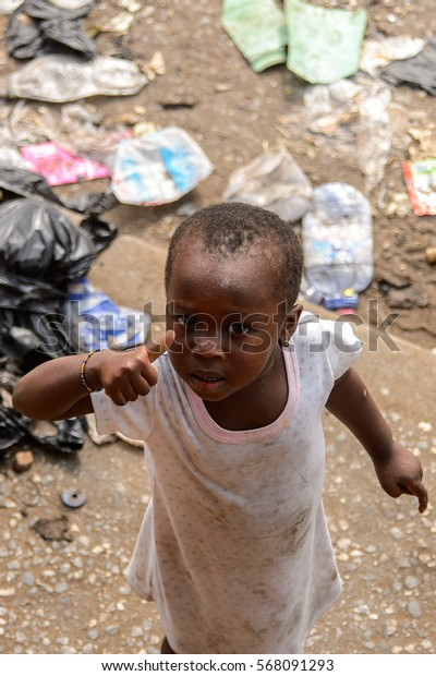 ACCRA, GHANA - JAN 8, 2017: Unidentified Ghanaian little girl in white dress shows her finger. Children of Ghana suffer of poverty due to the economic situation