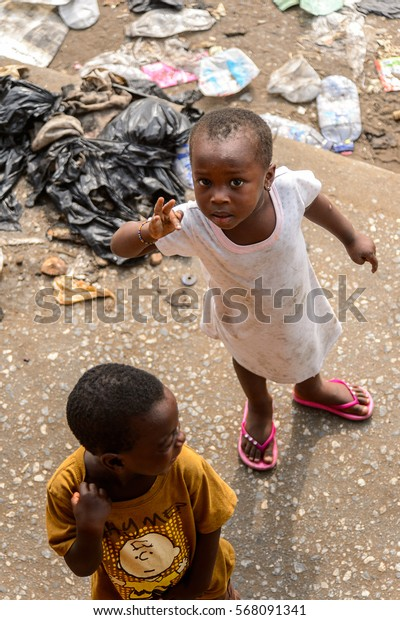 ACCRA, GHANA - JAN 8, 2017: Unidentified Ghanaian little kids play in the trash on the street. Children of Ghana suffer of poverty due to the economic situation