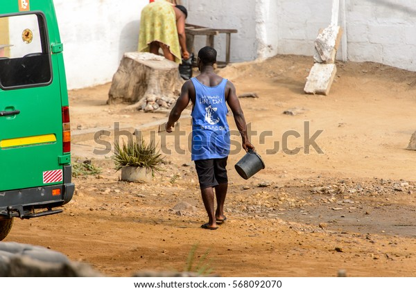 ACCRA, GHANA - JAN 8, 2017: Unidentified Ghanaian athletic man in blue shirt carries a bucket. People of Ghana suffer of poverty due to the economic situation
