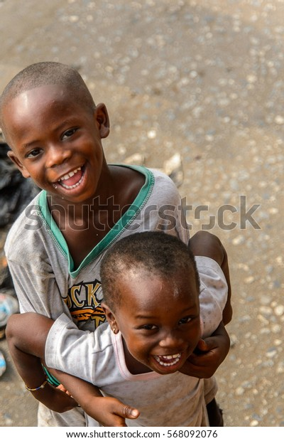 ACCRA, GHANA - JAN 8, 2017: Unidentified Ghanaian brother and sister smile on the street. Children of Ghana suffer of poverty due to the economic situation