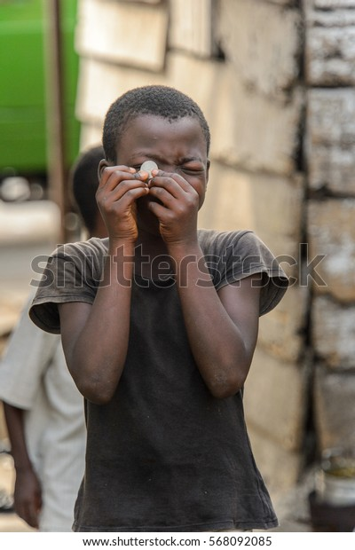 ACCRA, GHANA - JAN 8, 2017: Unidentified Ghanaian little girl holds a coin in her hand. Children of Ghana suffer of poverty due to the economic situation