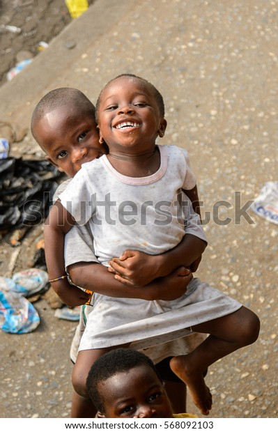 ACCRA, GHANA - JAN 8, 2017: Unidentified Ghanaian boy holds his little sister in his hands. Children of Ghana suffer of poverty due to the economic situation