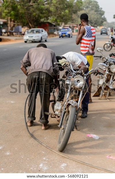 ACCRA, GHANA - JAN 8, 2017: Unidentified Ghanaian two men stand near the motocycle on the street. People of Ghana suffer of poverty due to the economic situation