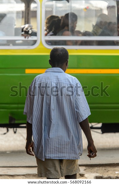 ACCRA, GHANA - JAN 8, 2017: Unidentified Ghanaian man stands in front of the green vehicle. People of Ghana suffer of poverty due to the economic situation