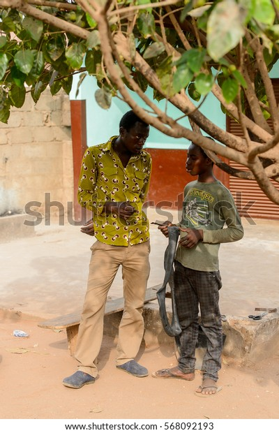 ACCRA, GHANA - JAN 8, 2017: Unidentified Ghanaian two men talk about something on the street. People of Ghana suffer of poverty due to the economic situation
