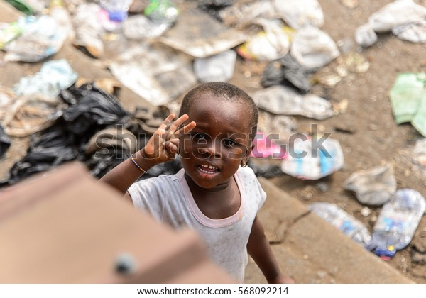 ACCRA, GHANA - JAN 8, 2017: Unidentified Ghanaian little girl in white dress shows her fingers. Children of Ghana suffer of poverty due to the economic situation