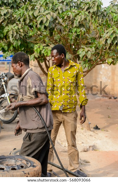 ACCRA, GHANA - JAN 8, 2017: Unidentified Ghanaian men stand on the street. People of Ghana suffer of poverty due to the economic situation