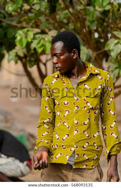 ACCRA, GHANA - JAN 8, 2017: Unidentified Ghanaian man in green shirt stand on the street. People of Ghana suffer of poverty due to the economic situation