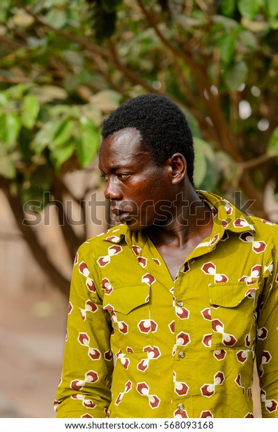 ACCRA, GHANA - JAN 8, 2017: Unidentified Ghanaian man in green shirt look away on the street. People of Ghana suffer of poverty due to the economic situation