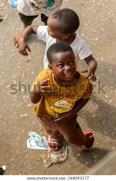ACCRA, GHANA - JAN 8, 2017: Unidentified Ghanaian little children play in the trash on the street. Children of Ghana suffer of poverty due to the economic situation
