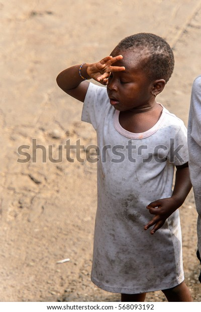 ACCRA, GHANA - JAN 8, 2017: Unidentified Ghanaian little girl in dirty white dress with closed eyes. Children of Ghana suffer of poverty due to the economic situation