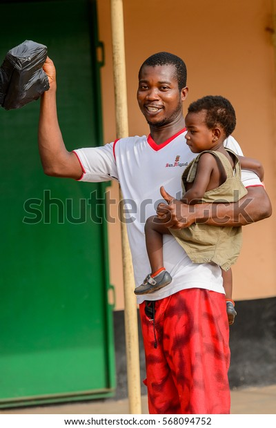 ACCRA, GHANA - JAN 8, 2017: Unidentified Ghanaian man carries a baby girl in his hand. People of Ghana suffer of poverty due to the economic situation