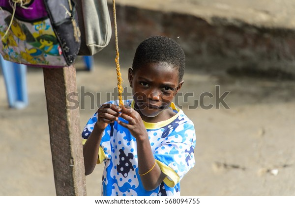 ACCRA, GHANA - JAN 8, 2017: Unidentified Ghanaian little boy in colored shirt holds on the rope on the street . Children of Ghana suffer of poverty due to the economic situation