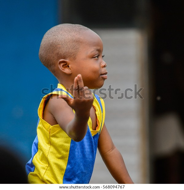 ACCRA, GHANA - JAN 8, 2017: Unidentified Ghanaian boy points the fingers in yellow and blue shirt. Children of Ghana suffer of poverty due to the economic situation