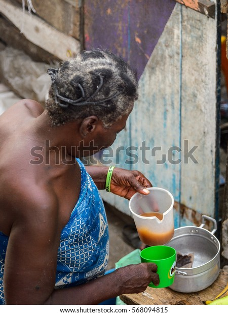 ACCRA, GHANA - JAN 8, 2017: Unidentified Ghanaian old woman with grey hair holds a bowl with some liquids. People of Ghana suffer of poverty due to the economic situation