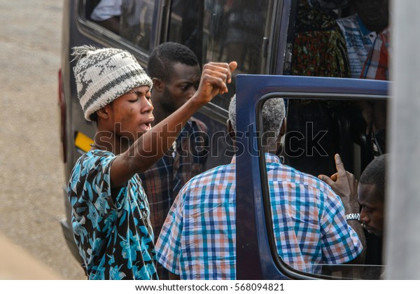 ACCRA, GHANA - JAN 8, 2017: Unidentified Ghanaian men talk about something near the car. People of Ghana suffer of poverty due to the economic situation