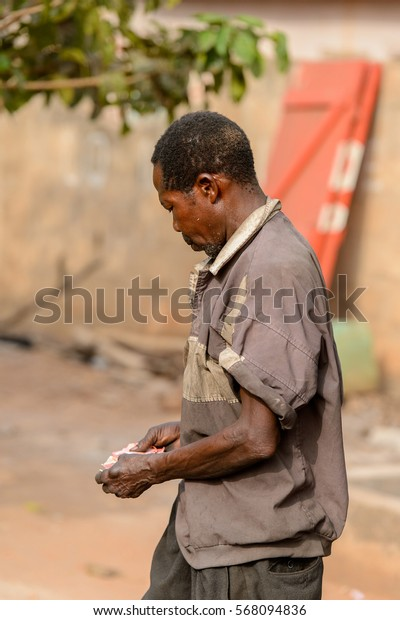 ACCRA, GHANA - JAN 8, 2017: Unidentified Ghanaian old man counts money in his hands. People of Ghana suffer of poverty due to the economic situation