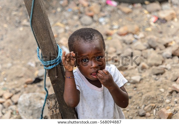 ACCRA, GHANA - JAN 8, 2017: Unidentified Ghanaian little girl tries to put her fingers into the mouth near the wooden pole. Children of Ghana suffer of poverty due to the economic situation