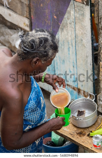 ACCRA, GHANA - JAN 8, 2017: Unidentified Ghanaian old woman with grey hair pours the liquids into a glass. People of Ghana suffer of poverty due to the economic situation