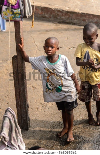 ACCRA, GHANA - JAN 8, 2017: Unidentified Ghanaian barefoot little boy holds on the wooden pole. Children of Ghana suffer of poverty due to the economic situation