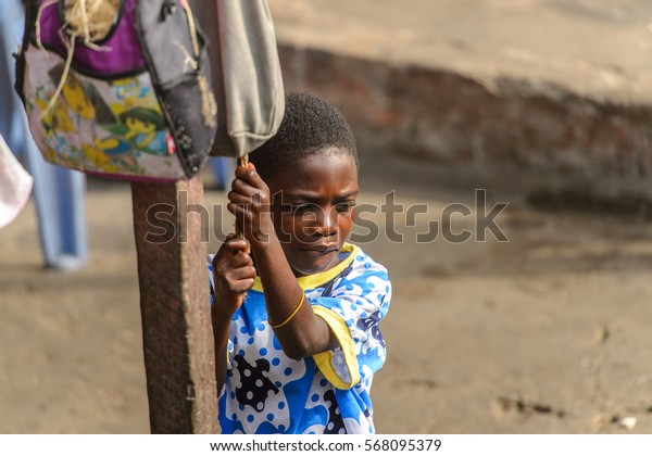 ACCRA, GHANA - JAN 8, 2017: Unidentified Ghanaian little boy   pulls the rope on the street . Children of Ghana suffer of poverty due to the economic situation