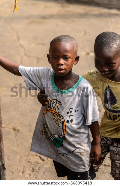 ACCRA, GHANA - JAN 8, 2017: Unidentified Ghanaian little boy hugs his friend on the street. Children of Ghana suffer of poverty due to the economic situation