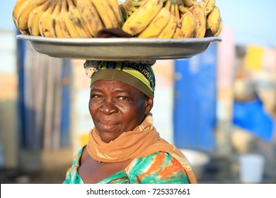 ACCRA - GHANA - JULY 20, 2017: Unidentified market woman carries a plate with bananas on her head on July 20, 2017 in Accra, Ghana