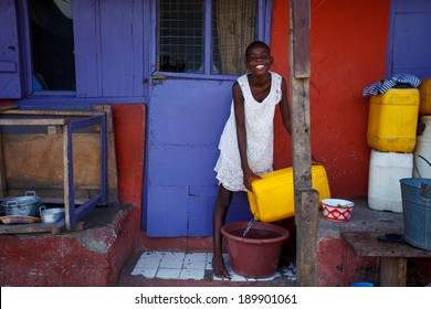ACCRA, GHANA - MARCH 18: Unidentified African girl pouring water on March 18, 2014 in Teshie community, Accra, Ghana. Teshie is the famous fishing community in Ghana.
