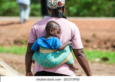 ACCRA, GHANA - MARCH 3, 2012: Unidentified Ghanaian little baby boy on his mothers back in Ghana. People of Ghana suffer of poverty due to the unstable economic situation