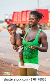 ACCRA, GHANA - MARCH 5, 2012: Unidentified Ghanaian baby boy on his mother arms in the street in Ghana. Children of Ghana suffer of poverty due to the unstable economic situation
