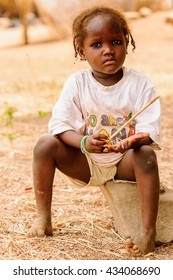 ACCRA, GHANA - MARCH 6, 2012: Unidentified Ghanaian girl with pigtails sits in the street in Ghana. Children of Ghana suffer of poverty due to the unstable economic situation