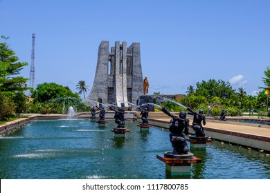 ACCRA,GHANA - APRIL 11 2018: Looking through water fountains in Kwame Nkrumah Memorial Park to the marble Mausoleum and gold statue to the Ghanaian president