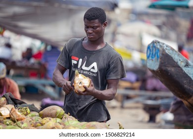 ACCRA,GHANA- FEBRUARY 12, 2019: Coconut seller peeling off coconut in Accra central.