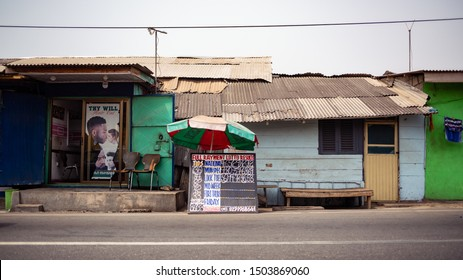 ACCRA,GHANA- FEBRUARY 12, 2019: Front view of a typical home and place of business setup in Jamestown, one of the most historic towns in Accra. Showing a barbering shop and displayed lottery results