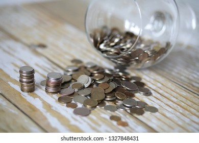Accumulated coins stacked in glass jars on the floor