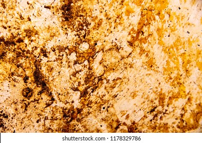 Accumulated dirt, grime, grease, and stains on the base of a steel cooking pan.