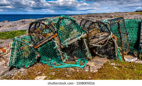 Accumulation of old and broken lobster / crab cages or fishing traps found on the coast in Inis Oirr island, the ocean in the background at Inisheer, an island in the west of the coast of Ireland