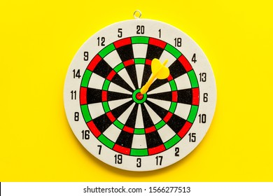 Accuracy of precision concept. Dartboard and arrows on yellow background top view copy space