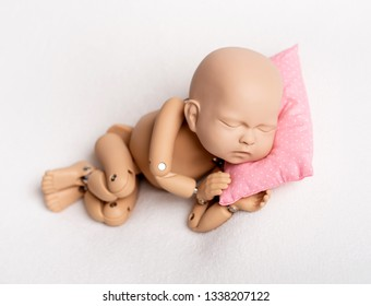 Accurate doll of newborn baby on pink pillow for photo practicing, on white background