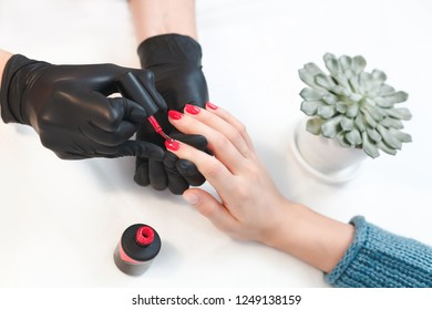 Accurate work of master on manicure in woman's salon. Coating red nail Polish. Gentle care.