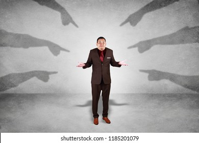 Accusation guilty business person. Asian businessman get upset with many fingers pointing at him over grey background