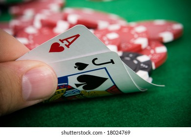 Ace of hearts and black jack with red poker chips in the background.