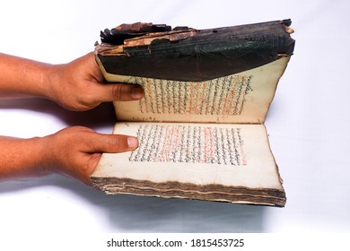 Aceh, Indonesia, 10/9/2020: Hands holding an antique Arabic script book with worn leather cover. Antiques in the collection of the Pedir Museum, Banda Aceh.