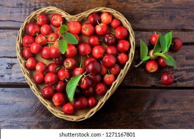 Acerola Cherry raw, fresh, in basket with heart shape on rustic wooden table, antioxidant fruits. Top View