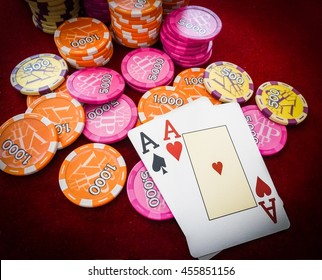Aces on red table with poker chips Vignetted