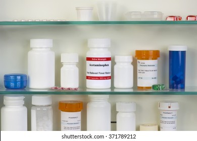 Acetaminophen container on glass shelf in home medicine cabinet.